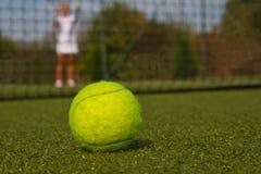 Pelota de tenis y silueta del jugador de tenis Imágenes de archivo libres de regalías