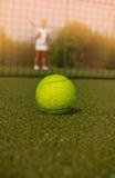 Pelota de tenis y silueta del jugador de tenis Foto de archivo