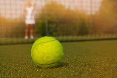Pelota de tenis y silueta del jugador de tenis en día del sammer Fotografía de archivo