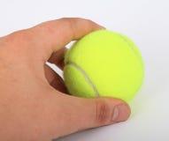 Pelota de tenis y una mano Foto de archivo libre de regalías