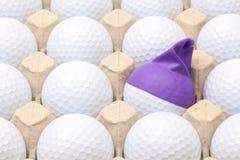 Pelotas de golf blancas en la caja para los huevos Pelota de golf con el casquillo divertido Fotos de archivo libres de regalías