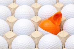 Pelotas de golf blancas en la caja para los huevos Pelota de golf con el casquillo divertido Fotografía de archivo libre de regalías