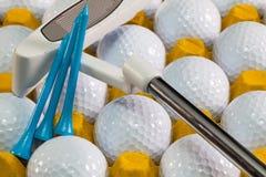 Pelotas de golf blancas en la caja y el putter amarillos del golf Fotos de archivo libres de regalías