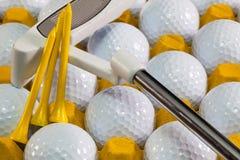 Pelotas de golf blancas en la caja y el putter amarillos del golf Imagen de archivo libre de regalías