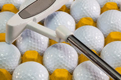 Pelotas de golf blancas en la caja y el putter amarillos del golf Imágenes de archivo libres de regalías