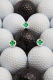 Pelotas de golf blancas y negras y camisetas de madera Imágenes de archivo libres de regalías