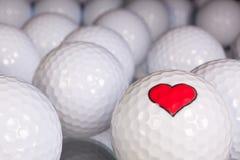 Pelotas de golf con símbolo del amor Imagenes de archivo