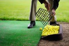 Pelotas de golf que vierten fuera de cesta Fotografía de archivo libre de regalías