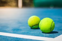 Pelotas de tenis ante el tribunal en el piso azul de la esquina fotos de archivo