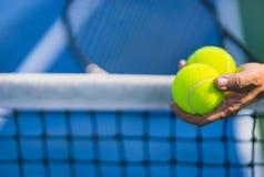 Pelotas de tenis asiáticas viejas del control dos del hombre en mano izquierda, foco selectivo, campo de tenis borroso de la esta Fotos de archivo