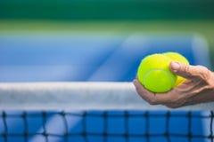 Pelotas de tenis asiáticas viejas del control dos del hombre en mano izquierda, foco selectivo, red borrosa y campo de tenis azul Imágenes de archivo libres de regalías