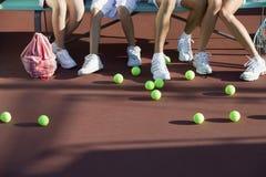 Pelotas de tenis dispersadas en corte de los pies de gente Imagen de archivo libre de regalías