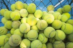Pelotas de tenis en la cesta en campo de tenis Fotografía de archivo