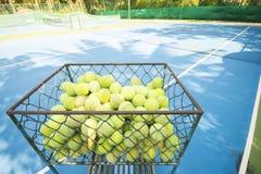 Pelotas de tenis en la cesta en el campo de tenis Foto de archivo libre de regalías