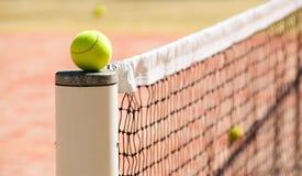 Pelotas de tenis en la corte cerca de redes del tenis Foto de archivo