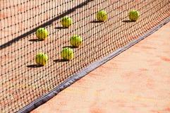 Pelotas de tenis en la corte cerca de redes del tenis Imagenes de archivo