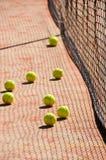 Pelotas de tenis en la corte cerca de redes del tenis Fotografía de archivo libre de regalías