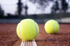 Pelotas de tenis en la pista de tenis de la arcilla imagen de archivo libre de regalías