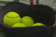 Pelotas de tenis en sombrero negro del deporte imágenes de archivo libres de regalías