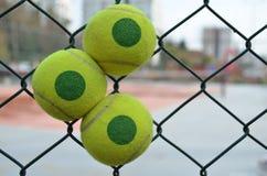 Pelotas de tenis en una reja del ` s del campo de tenis Fotos de archivo libres de regalías