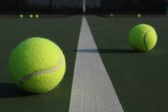 Pelotas de tenis que montan la línea de la corte a horcajadas Imagenes de archivo