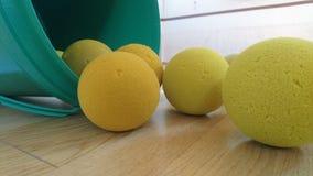 Pelotas de tenis suaves que caen del cubo Imagen de archivo