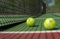 Pelotas de tenis verdes, amarillas en campo de tenis Imagen de archivo libre de regalías