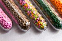 pelotas plásticas Tintura polimérico em uns tubos de ensaio no fundo cinzento Foto de Stock