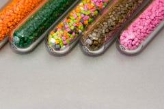 pelotas plásticas Tintura polimérico em uns tubos de ensaio no fundo cinzento Fotos de Stock