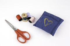 Pelote à épingles avec des aiguilles, des boutons, des ciseaux et des fils Photographie stock libre de droits