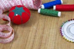 Pelote à épingles rouge, bande et fils colorés avec l'aiguille Photographie stock libre de droits