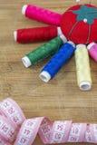 Pelote à épingles rouge et plusieurs fils colorés comme soleil Photographie stock libre de droits