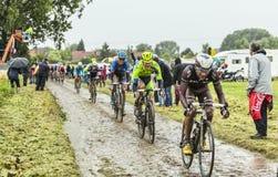 The Peloton on a Cobbled Road- Tour de France 2014. Ennevelin, France - July 09,2014: The peloton riding on a cobbled road during the stage 5 of Le Tour de Royalty Free Stock Photo