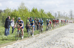 The Peloton on a Cobblestoned Road. Carrefour de l'Arbre,France-April 13,2014: The peloton,containing young cyclists, riding during a race of juniors on the Royalty Free Stock Photos