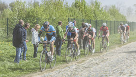 The Peloton on a Cobblestoned Road. Carrefour de l'Arbre,France-April 13,2014: The junior cyclist Enzo Wouters in front of a part of the peloton,containing young Stock Photo