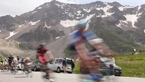 The Peloton on Col du Lautaret. COL DU LAUTARET,FRANCE - JUL 19: The peloton passing in blurred speed motion in front of beautiful mountains at Col du Lautaret stock footage