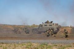 Peloton des soldats armés ainsi qu'un véhicule blindé sur le champ de bataille défendre leurs positions image stock