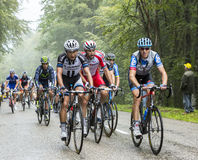 The Peloton in a Misty Day - Tour de France 2014. Col de Platzerwasel,France - July 14, 2014: The peloton on the climbing road to mountain pass Platzerwasel in Royalty Free Stock Photo