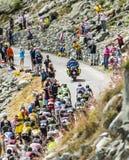The Peloton in Mountains. Col de la Croix de Fer, France - 23 July 2015: The peloton riding in a rocky natural environment at Col de la Croix de Fer in Alps Royalty Free Stock Photos