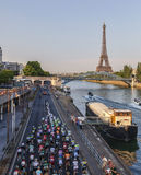 The Peloton in Paris. Paris, France- July 21st, 2013: The peloton riding on the Seine riverside near the Eiffel Tower during the last stage of the 100th edition Royalty Free Stock Photos