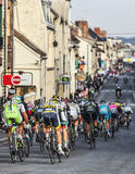 The Peloton- Paris Nice 2013 in Nemours. Nemours,France- March 4, 2013: Image of the peloton riding fastly in a narrow road in Nemours, during the first stage of Royalty Free Stock Images