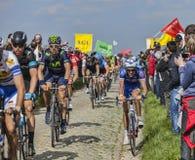 The Peloton- Paris Roubaix 2014. Carrefour de l'Arbre,France-April 13,2014: The peloton riding on the famous cobblestone sector Carrefour de l'Arbre in  Camphin Stock Images