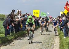 The Peloton- Paris Roubaix 2014. Carrefour de l'Arbre,France-April 13,2014: The peloton riding on the famous cobblestone sector Carrefour de l'Arbre in Camphin Royalty Free Stock Images