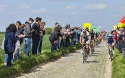 The Peloton- Paris Roubaix 2014. Carrefour de l'Arbre,France-April 13,2014: The peloton riding on the famous cobblestone sector Carrefour de l'Arbre in Camphin Stock Photography