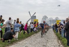 The Peloton - Paris-Roubaix 2018. Templeuve, France - April 08, 2018: The peloton riding on the cobblestone road in Templeuve in front of the traditional Vertain Stock Photos