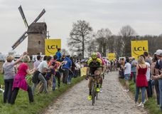 The Peloton - Paris-Roubaix 2018. Templeuve, France - April 08, 2018: The peloton riding on the cobblestone road in Templeuve in front of the traditional Vertain Royalty Free Stock Image