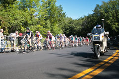 The Peloton racing with a police motor bike stock photo