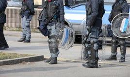 Pelotons des dirigeants de la police anti-émeute pendant les contrôles d'anti-terrorisme Photographie stock libre de droits