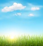 Pelouse d'herbe verte avec les nuages et le soleil sur le ciel bleu Image stock