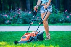Pelouse de fauchage de femme dans le jardin arrière résidentiel Photos libres de droits